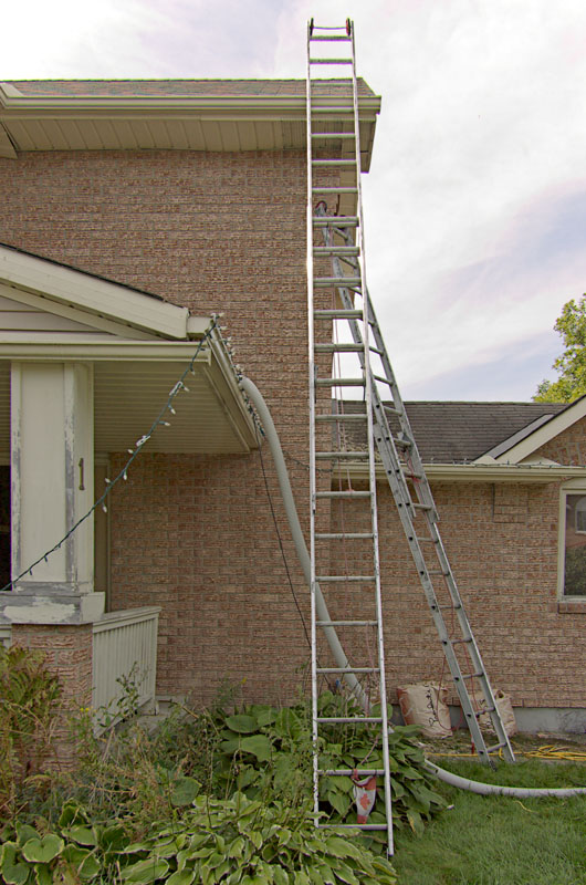 Tall ladders. Working at these angles has to be awkward. Note the hose going up through the bedroom window and into the attic. Blowing fresh insulation to R50.